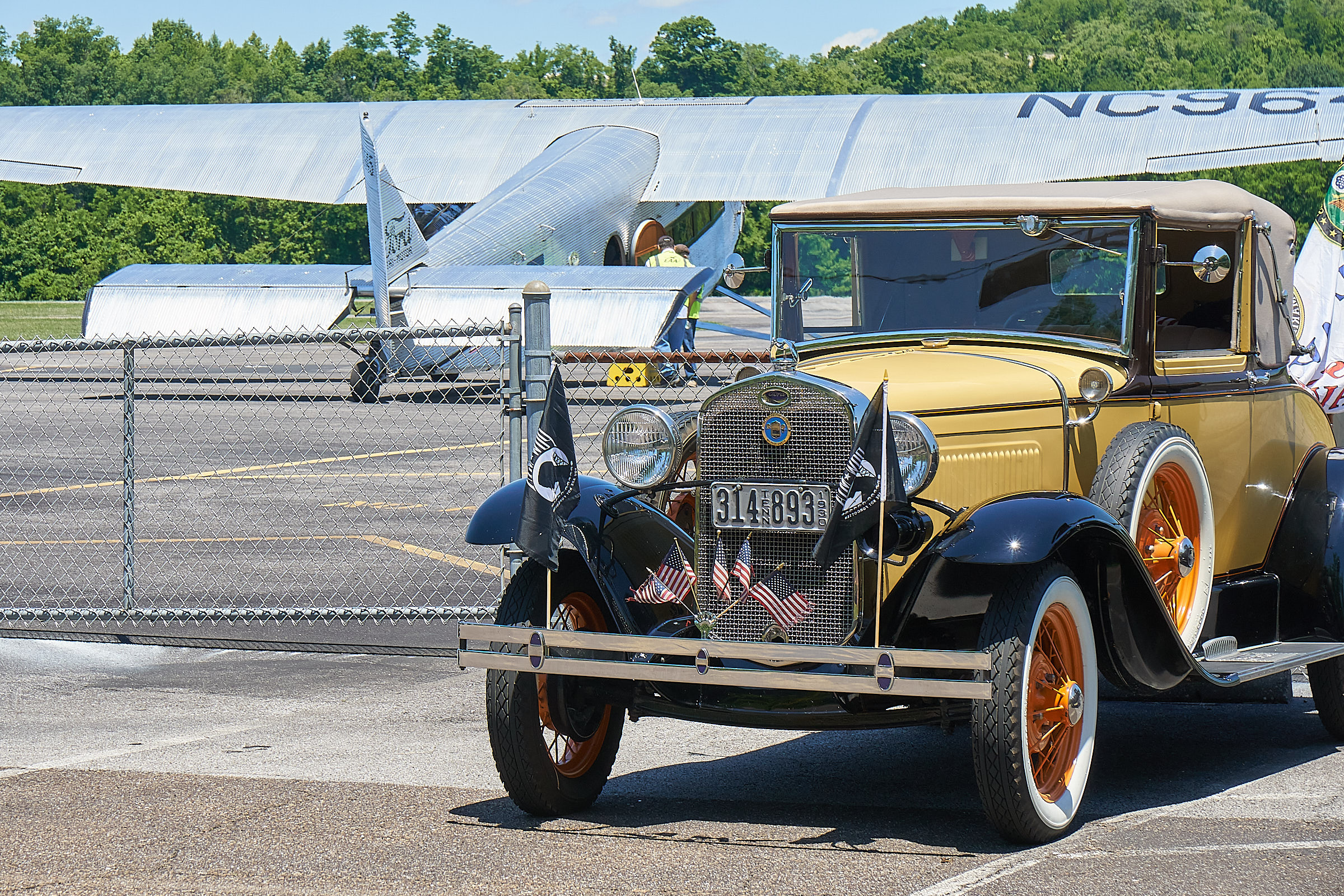 A club member car seen with the Ford Tri-motor airplane in the background